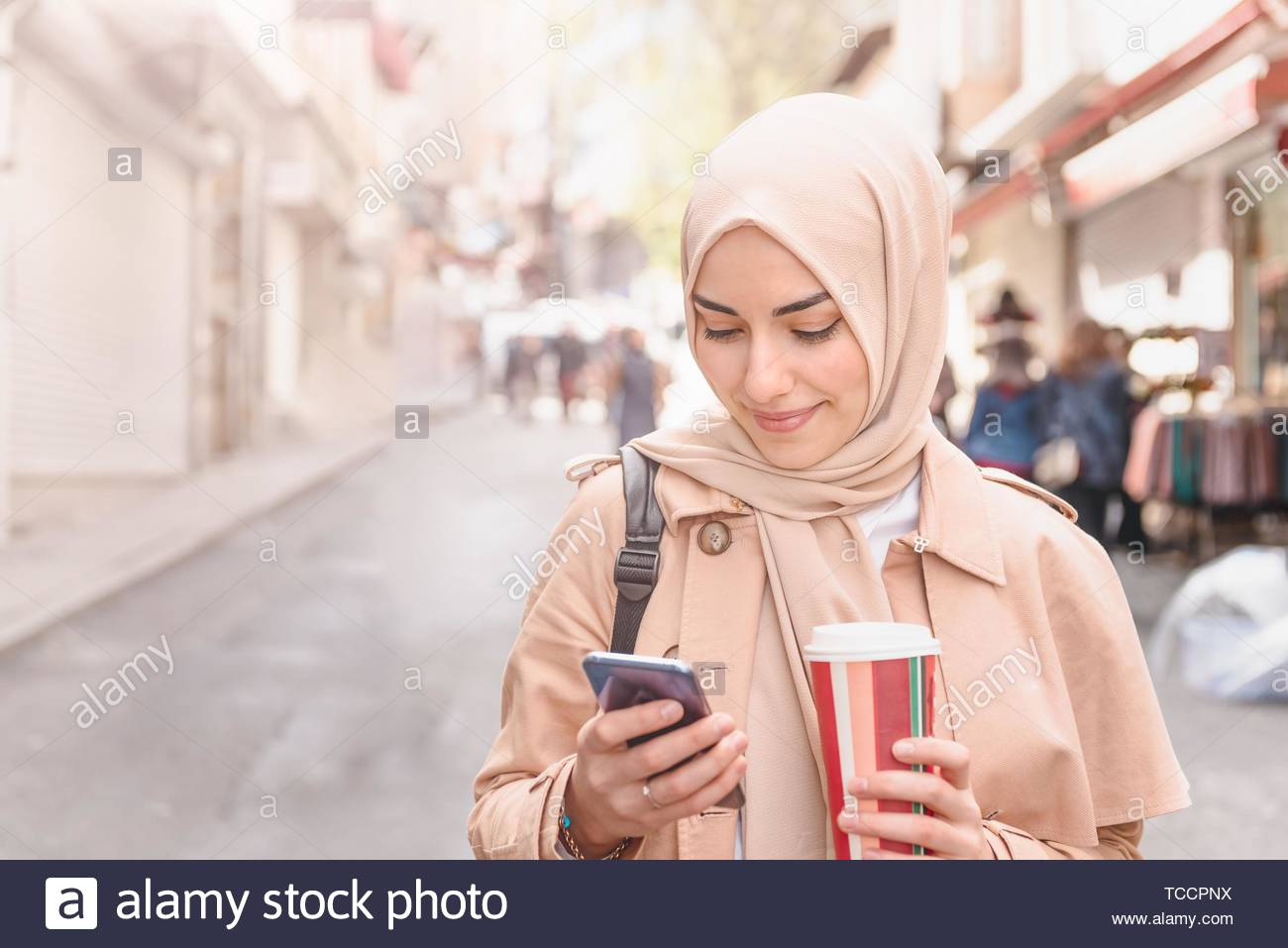 Beautiful Muslim woman in headscarf and fashionable modern trendy clothes with takeaway coffee uses smart phone while walking. Modern Muslim women Stock Photo