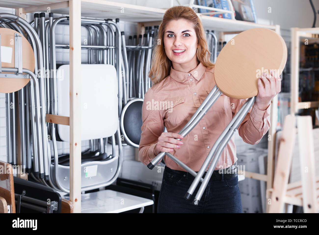 Smiling woman looking for new stylish tabouret for apartment in furniture salon - Stock Image