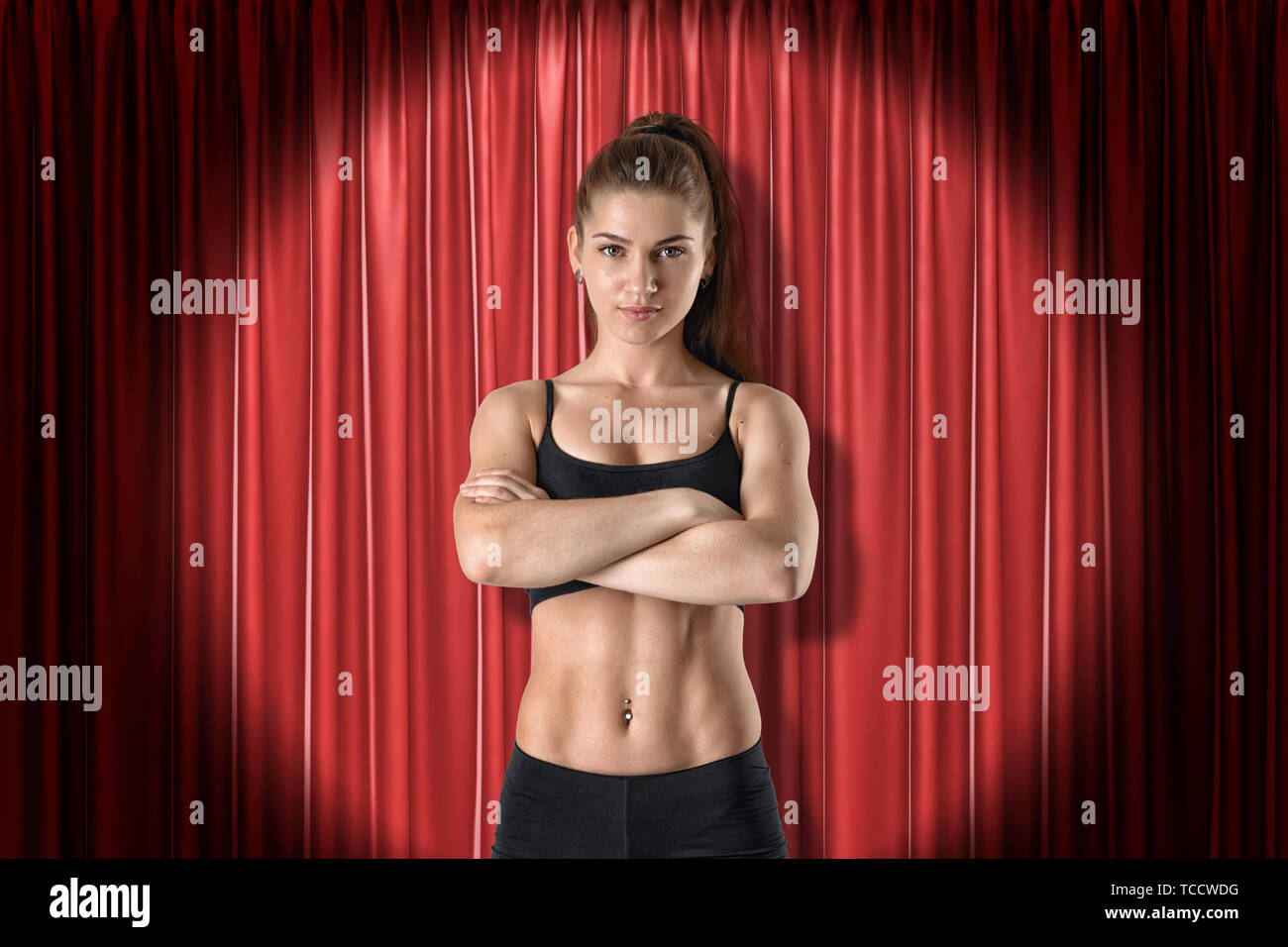 Front crop image of fit confident woman in crop top, standing with arms folded, in spotlight at red stage curtain. - Stock Image