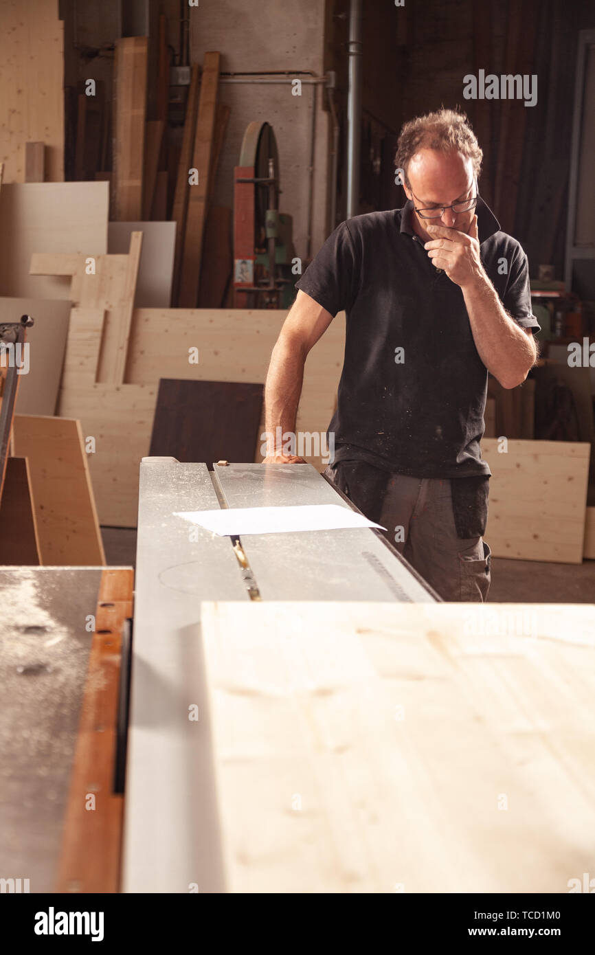 Carpenter or woodworker in his workshop standing looking thoughtfully down at the floor alongside his work bench with planks of wood - Stock Image