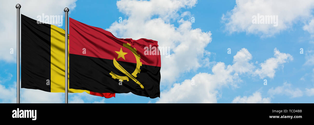 Belgium and Angola flag waving in the wind against white cloudy blue sky together. Diplomacy concept, international relations. - Stock Image