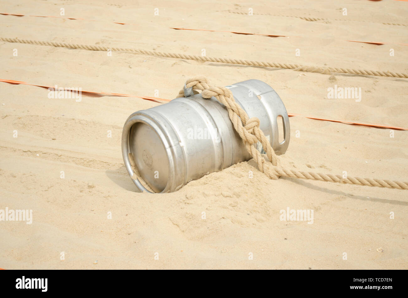 Sports competition with a barrel and a rope on the beach. - Stock Image