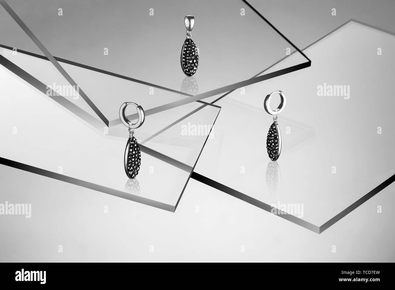 Silver earrings and pendant with stones. Studio still life composition. - Stock Image