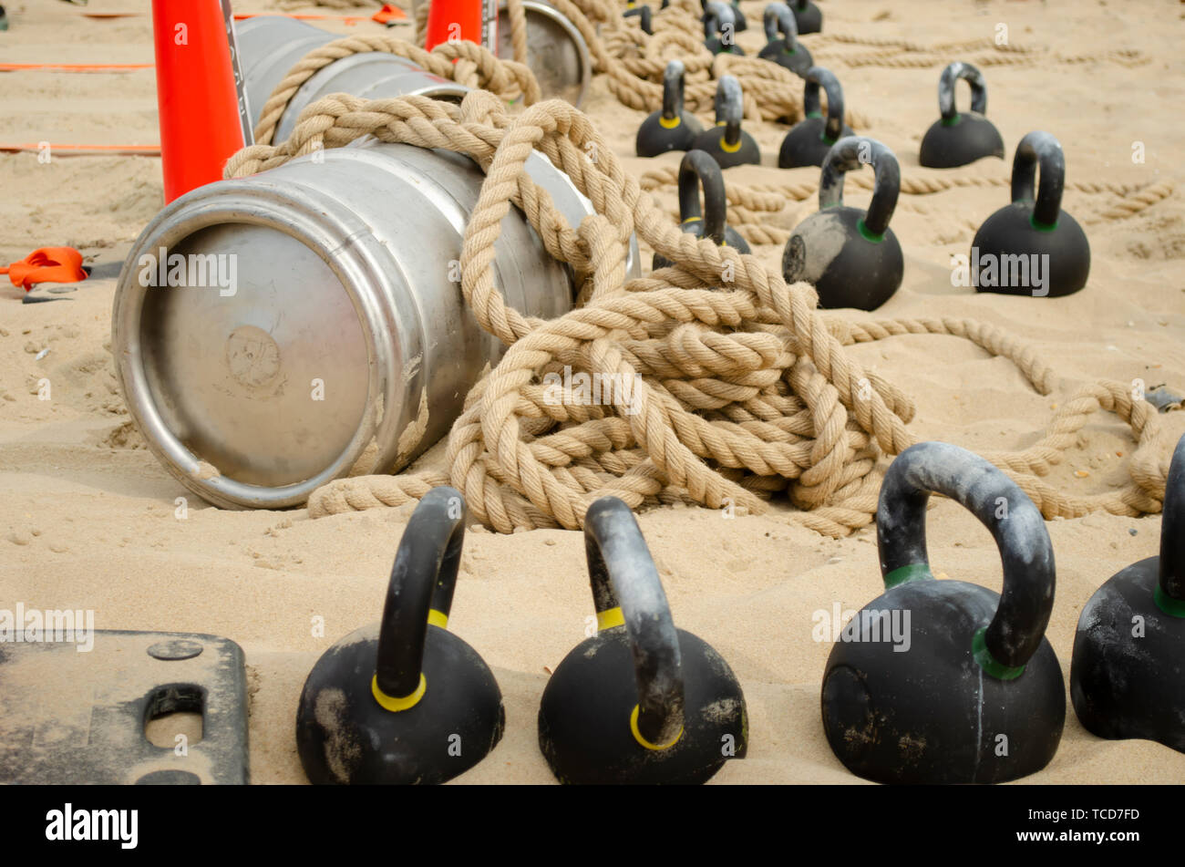 Barrel, tied with a rope and weights on the beach before a sporting event. - Stock Image