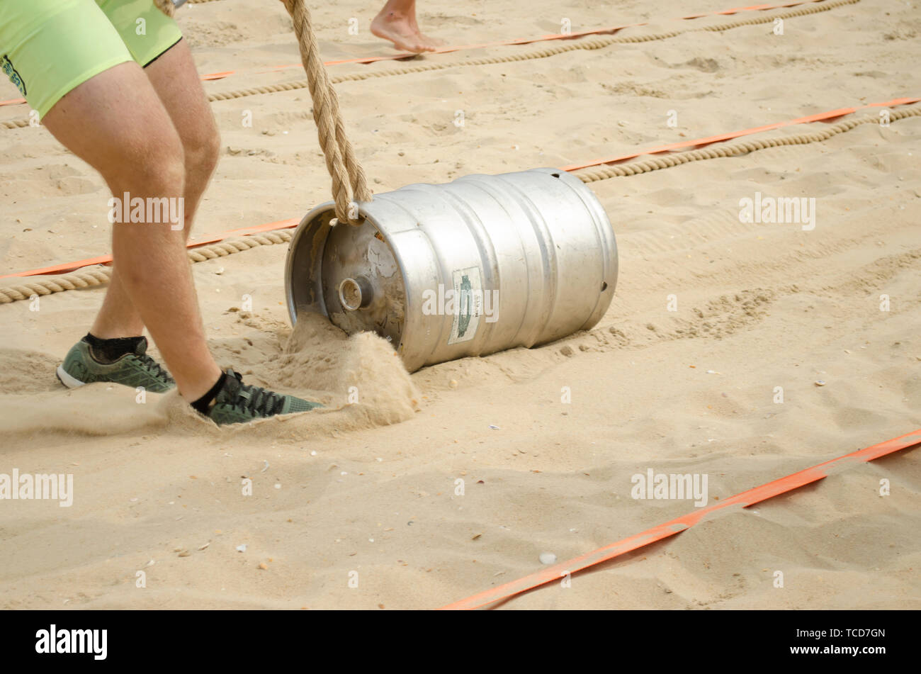 A man in shorts pulls a rope tied with rope over the sand. Sport competitions. - Stock Image