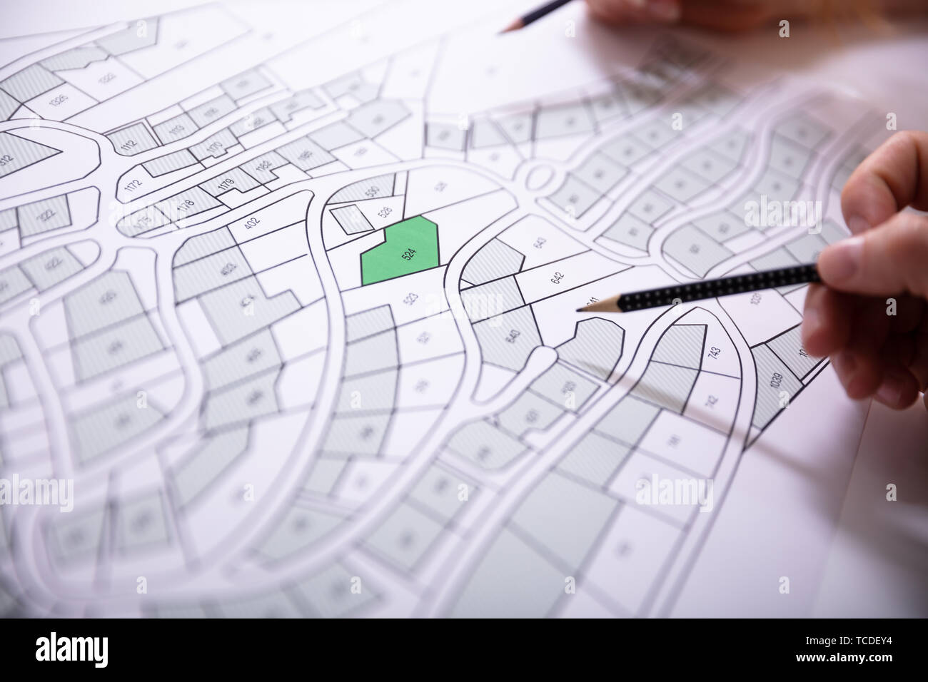Close-up Of Human Hand Holding Pencil Over Paper Cadastre Map - Stock Image