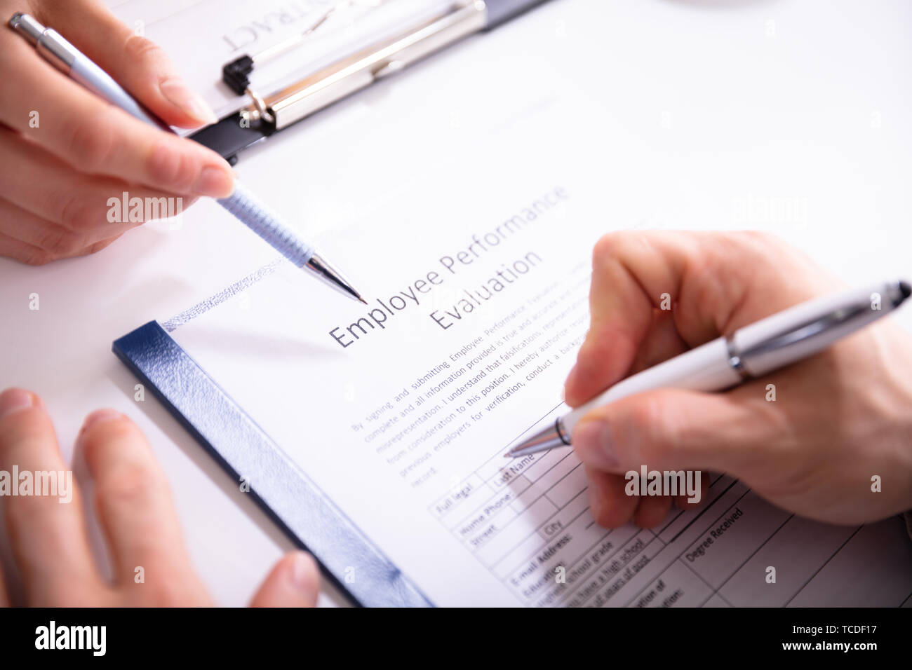 Close-up Of A Person Filling Performance Evaluation Form Of Employee Over Desk - Stock Image