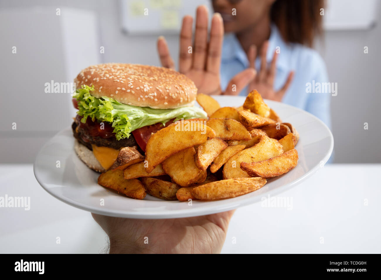 Young Woman Refusing Burger And French Fries On Plate - Stock Image