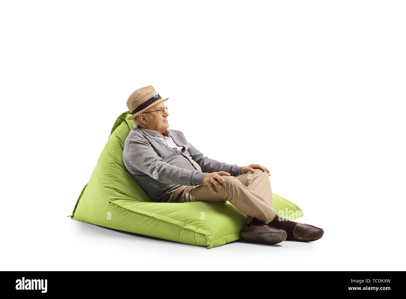 Elderly man resting on a bean-bag armchair isolated on white background - Stock Image
