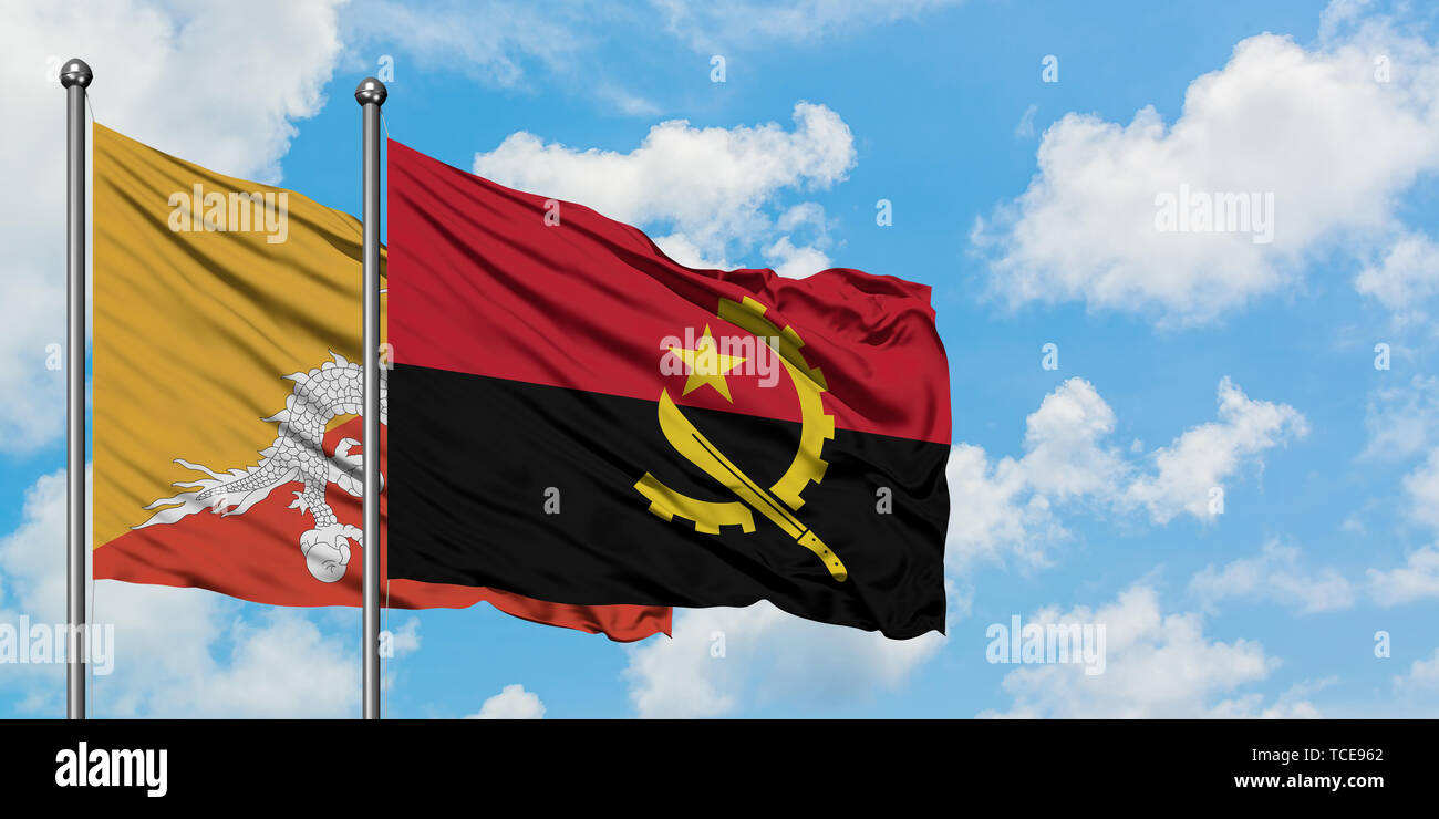 Bhutan and Angola flag waving in the wind against white cloudy blue sky together. Diplomacy concept, international relations. Stock Photo