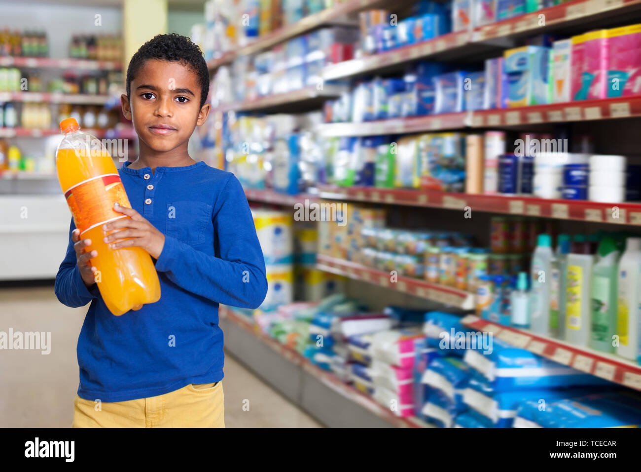 Cute African American preteen boy standing with bottles of soda drinks in supermarket - Stock Image