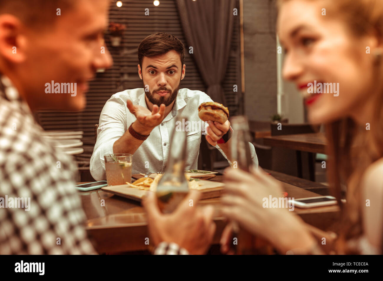 Showing dissatisfaction. Handsome dark-haired appealing young-adult male holding a burger and showing dissatisfaction with his flirting friends - Stock Image