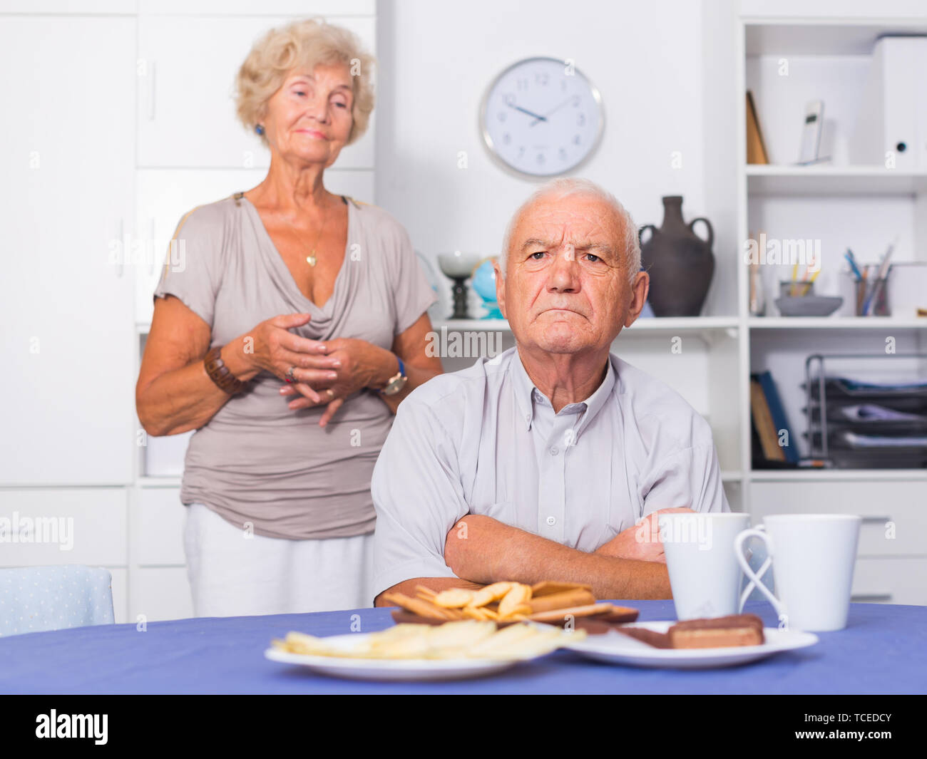 Senior man sitting at home table offended after quarrel with wife - Stock Image