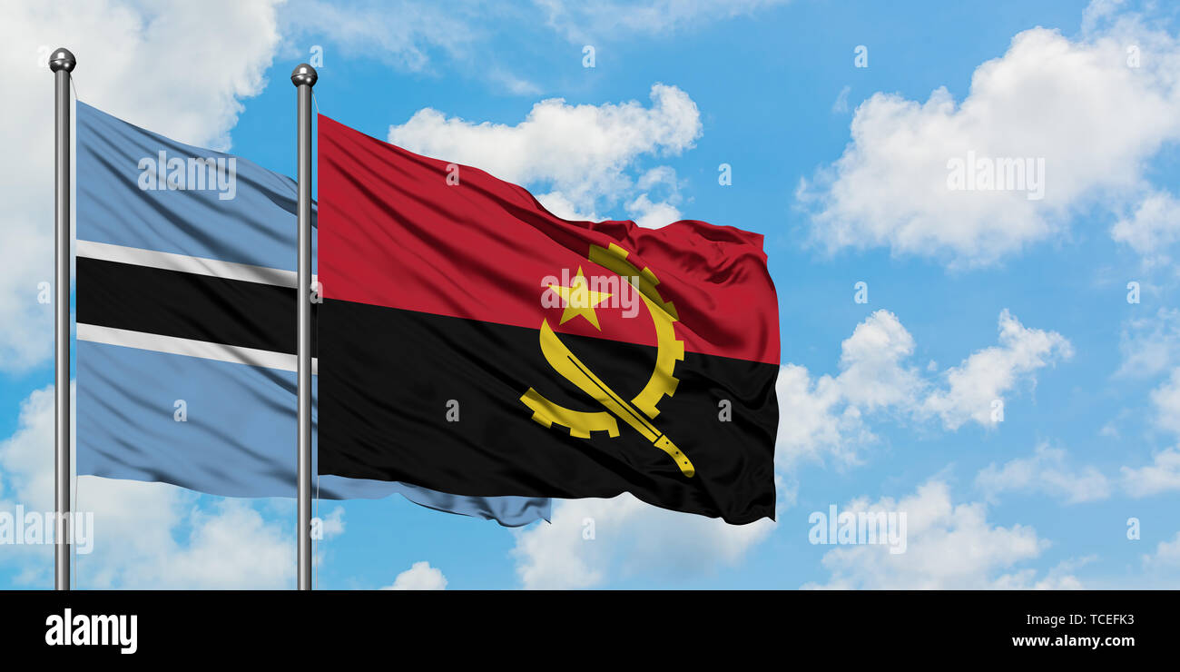 Botswana and Angola flag waving in the wind against white cloudy blue sky together. Diplomacy concept, international relations. - Stock Image