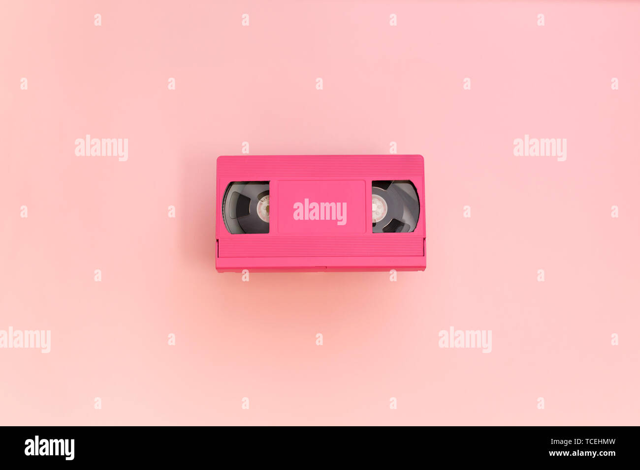 Pink video cassette tape on pink background. - Stock Image
