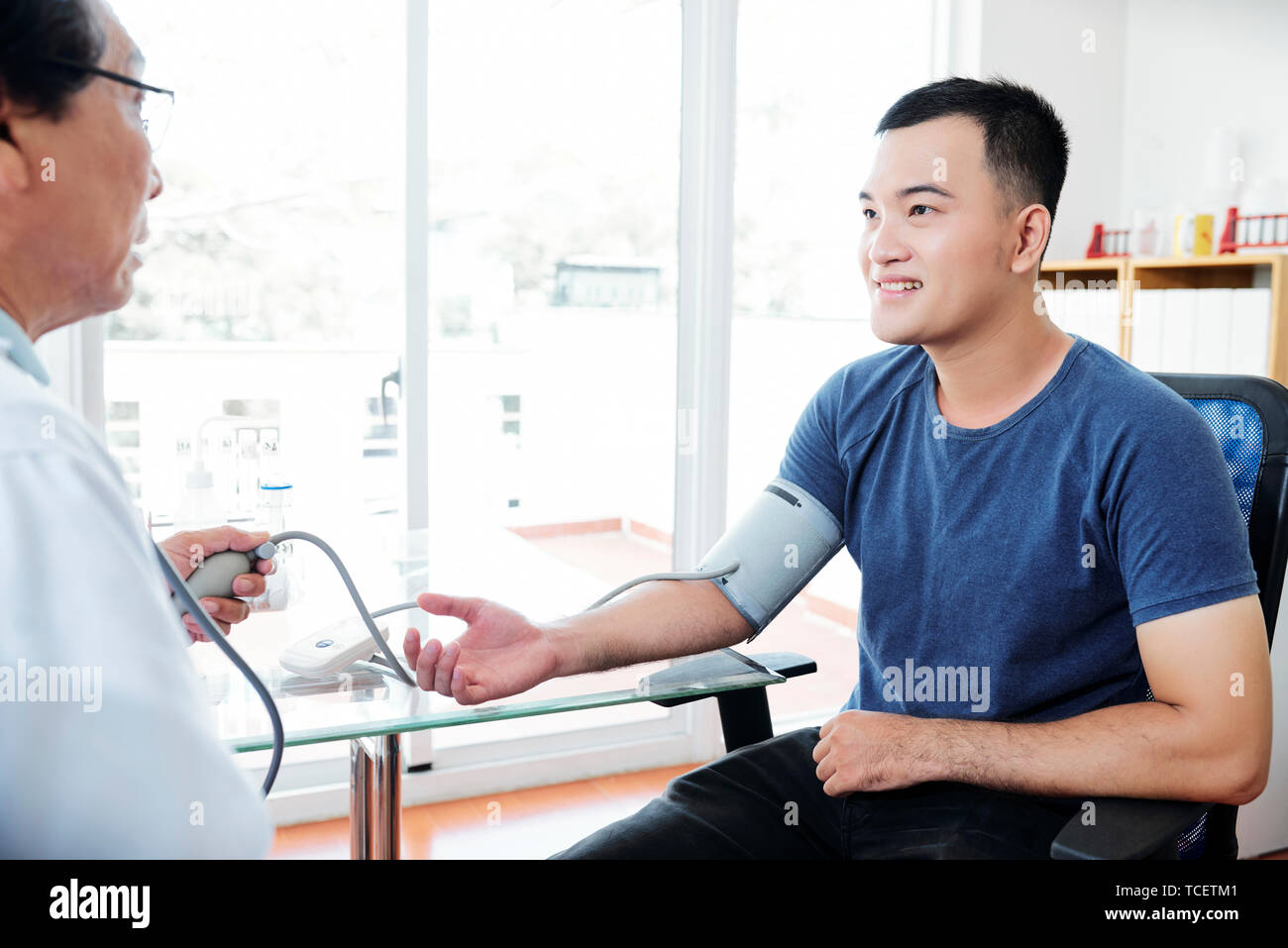 Doctor measuring blood pressure of young smiling Asian man - Stock Image