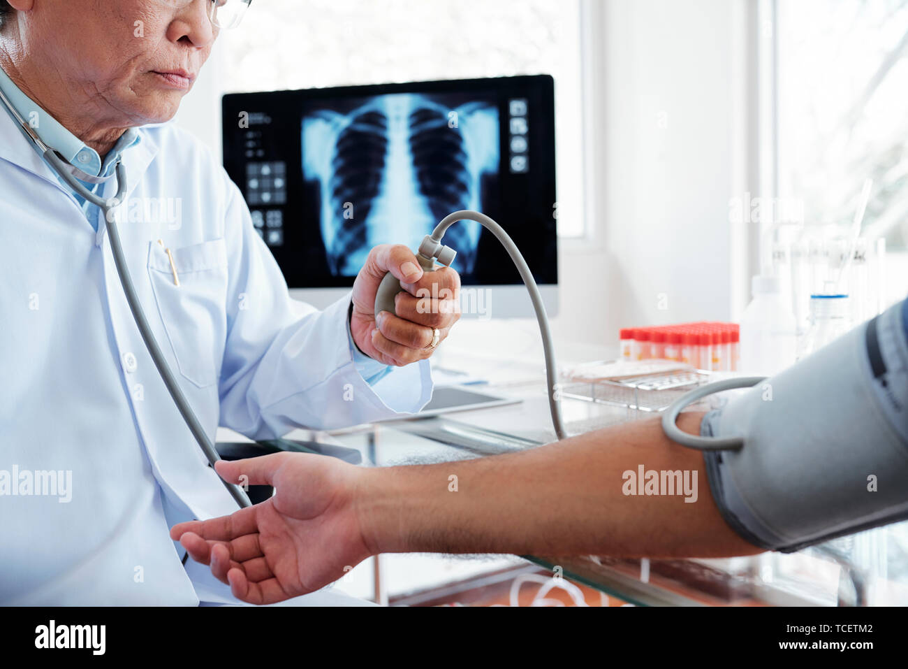 Serious general practitioner measuring blood pressure of young patient, chest x-ray on computer screen in background - Stock Image