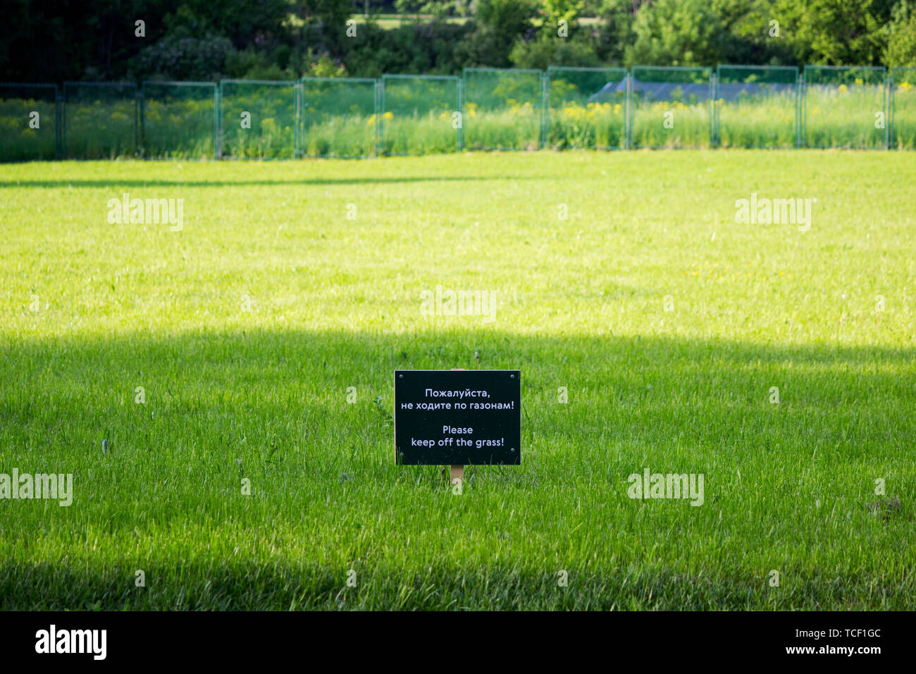 warning label on the meadow Gatchina park. Inscriptions in Russian and English: please do not walk on the lawns Stock Photo