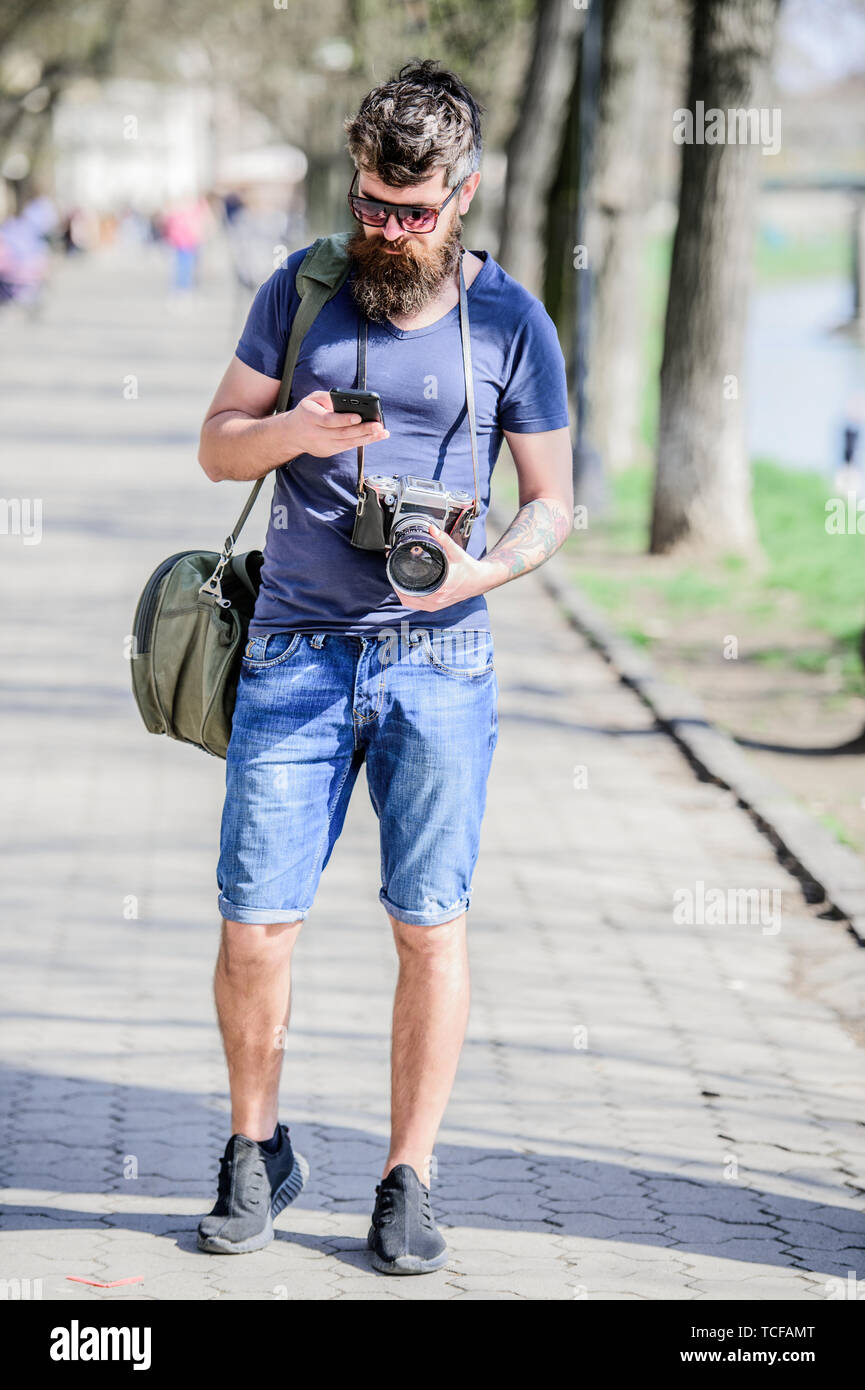 Photographer with beard and mustache. Tourist shooting photos. Content creator. Man bearded hipster photographer. Old but still good. Photographer hold vintage camera. Modern blogger. Manual settings. - Stock Image