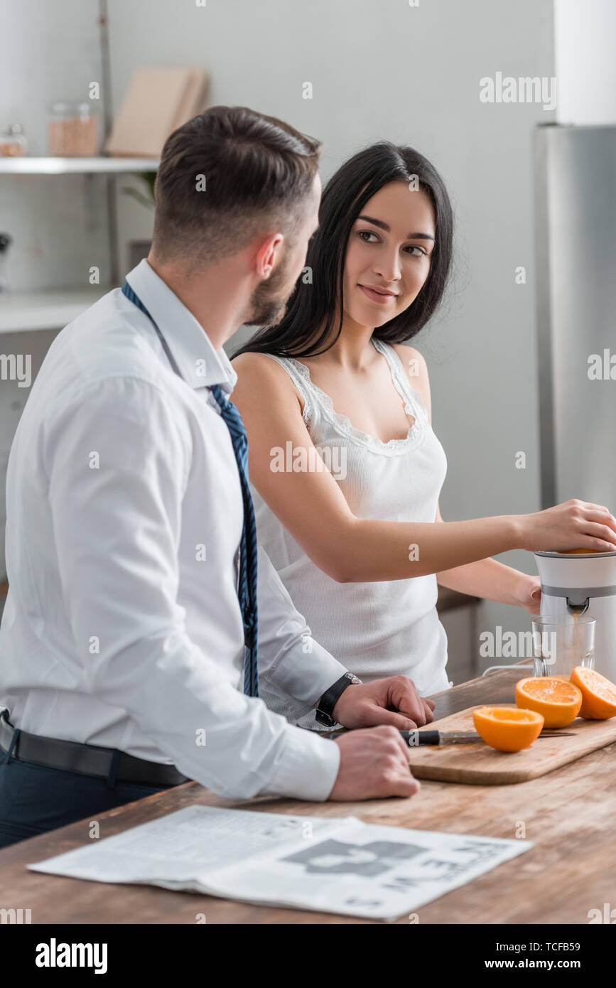 attractive brunette woman looking at man in suit while squeezing oranges in juicer Stock Photo
