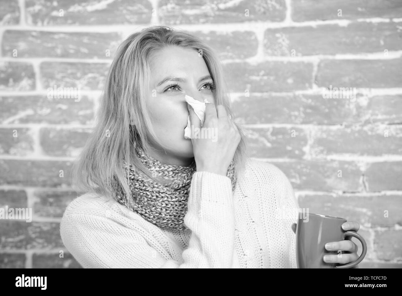 Runny nose and other symptoms of cold. Drinking plenty fluid important for ensuring speedy recovery from cold. Cold and flu remedies. Drink more liquid get rid of cold. Girl hold tea mug and tissue. - Stock Image