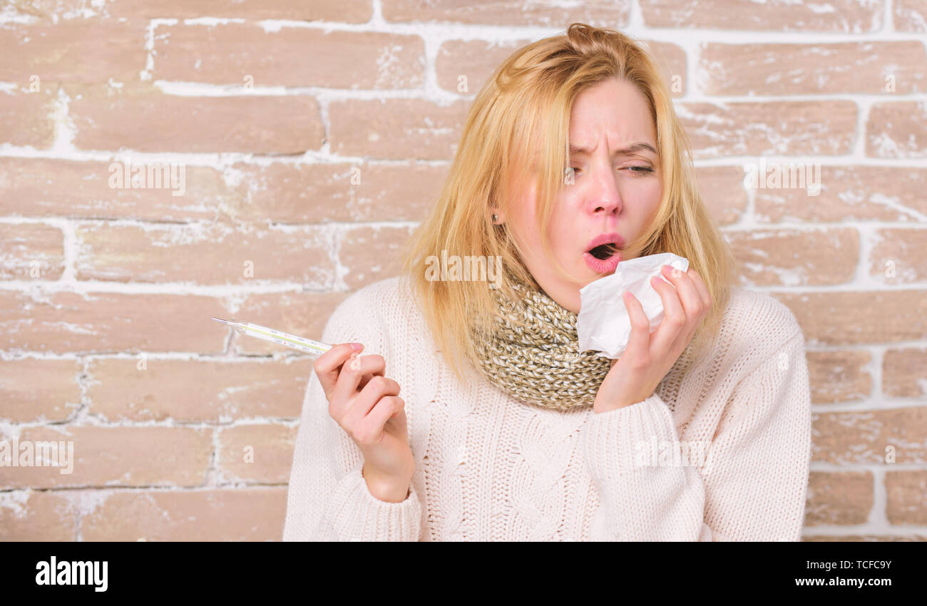 High temperature concept. Woman feels badly ill. How to bring fever down. Fever symptoms and causes. Sick girl with fever. Girl hold thermometer and tissue. Measure temperature. Break fever remedies. Stock Photo