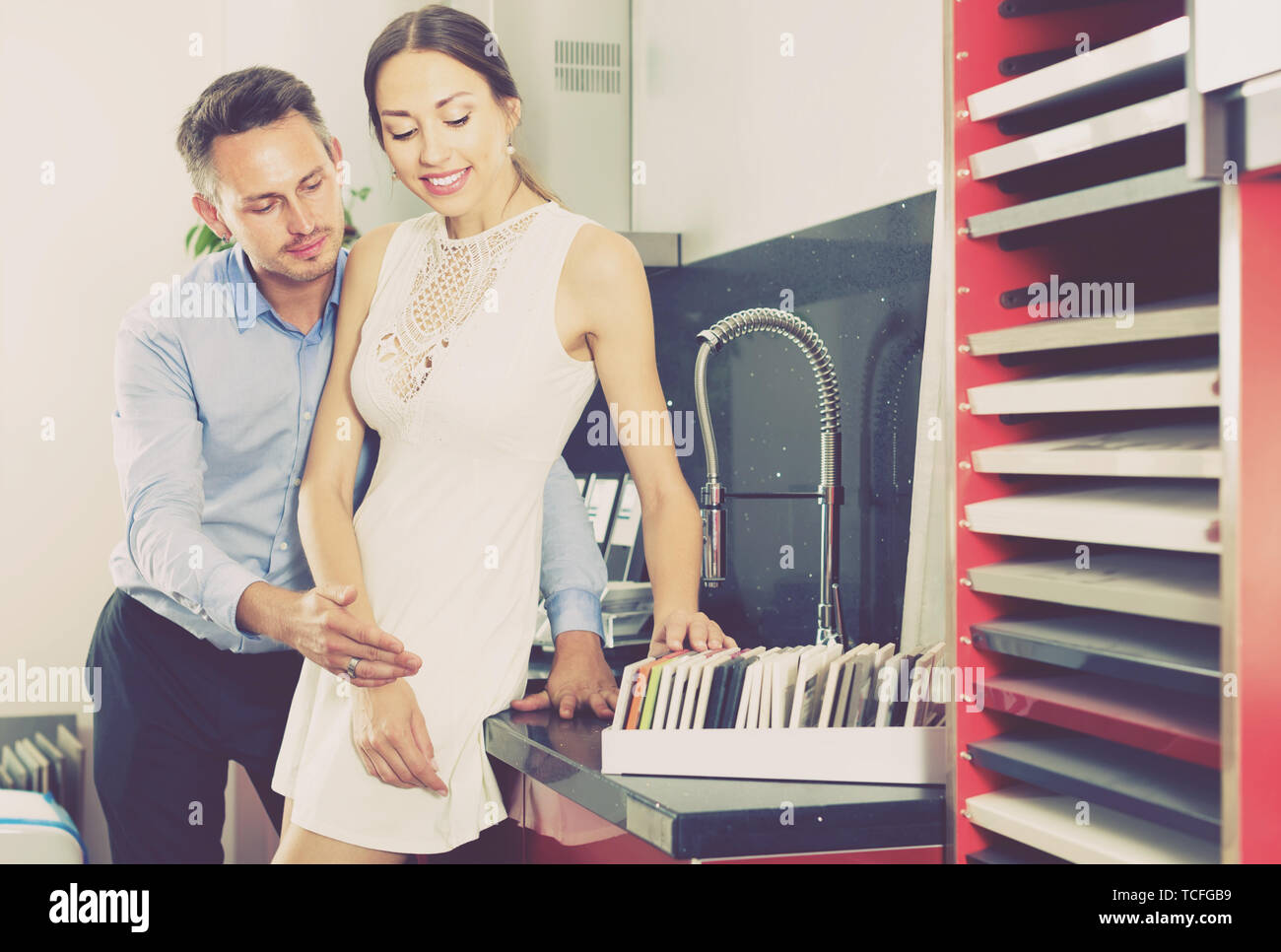 couple looking at modern kitchen tabletop in furniture workshop