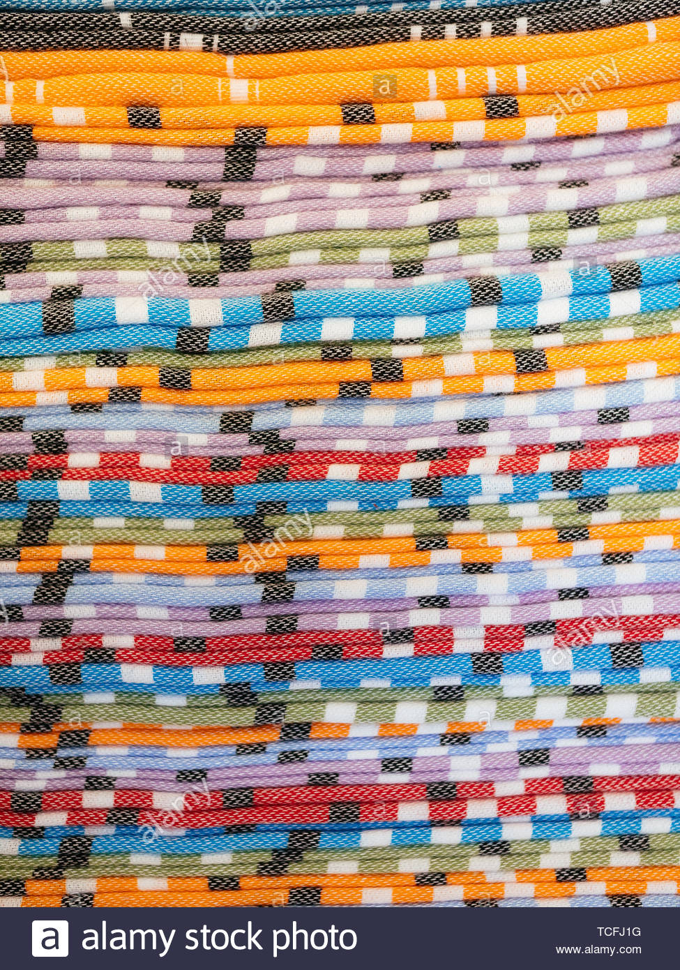 A pile of colorful traditional textiles photographed in the local handicraft market. - Stock Image