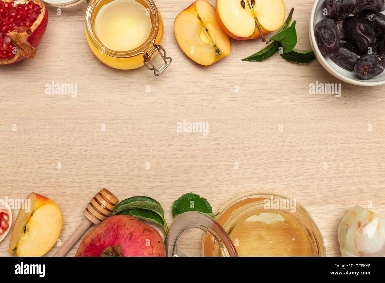 Honey, pomegranate, apple and dates on wooden board. Jewish New Year Rosh hashana celebration - Stock Image