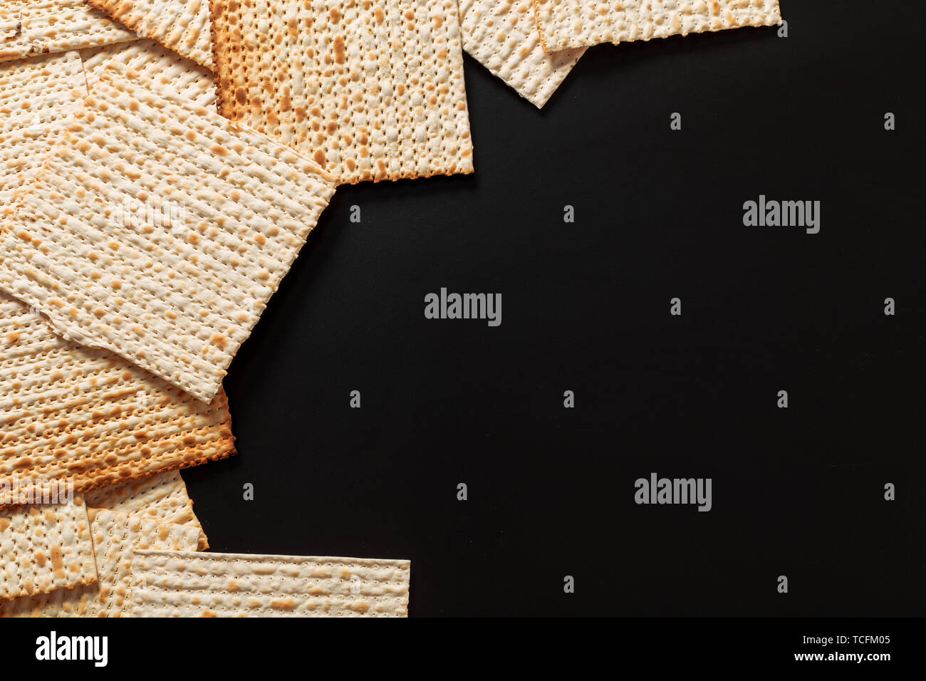 A photo of matzah or matza pieces  on black background. Matzah for the Jewish Passover holidays. Place for text, copy space - Stock Image