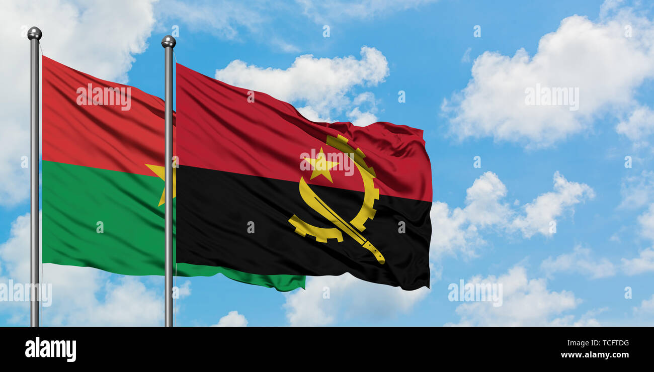 Burkina Faso and Angola flag waving in the wind against white cloudy blue sky together. Diplomacy concept, international relations. - Stock Image