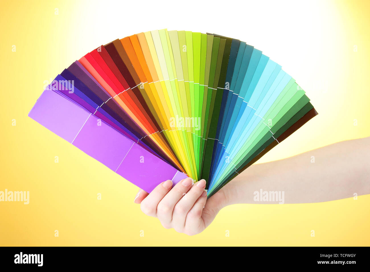 hand holding bright palette of colors on yellow background - Stock Image