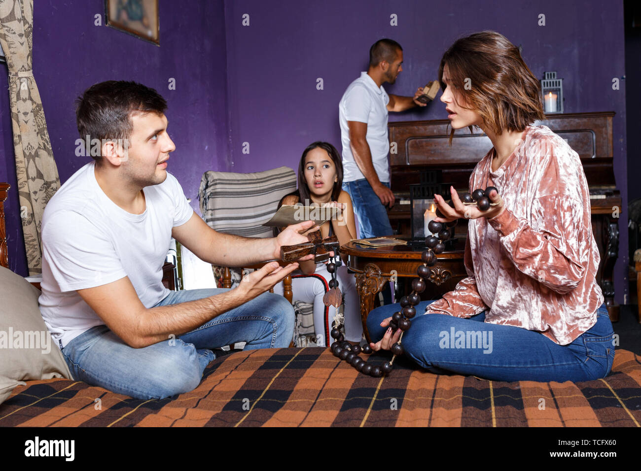 Young friends looking at wooden rosary while solving conundrum as detectives in quest room with old furnitures - Stock Image