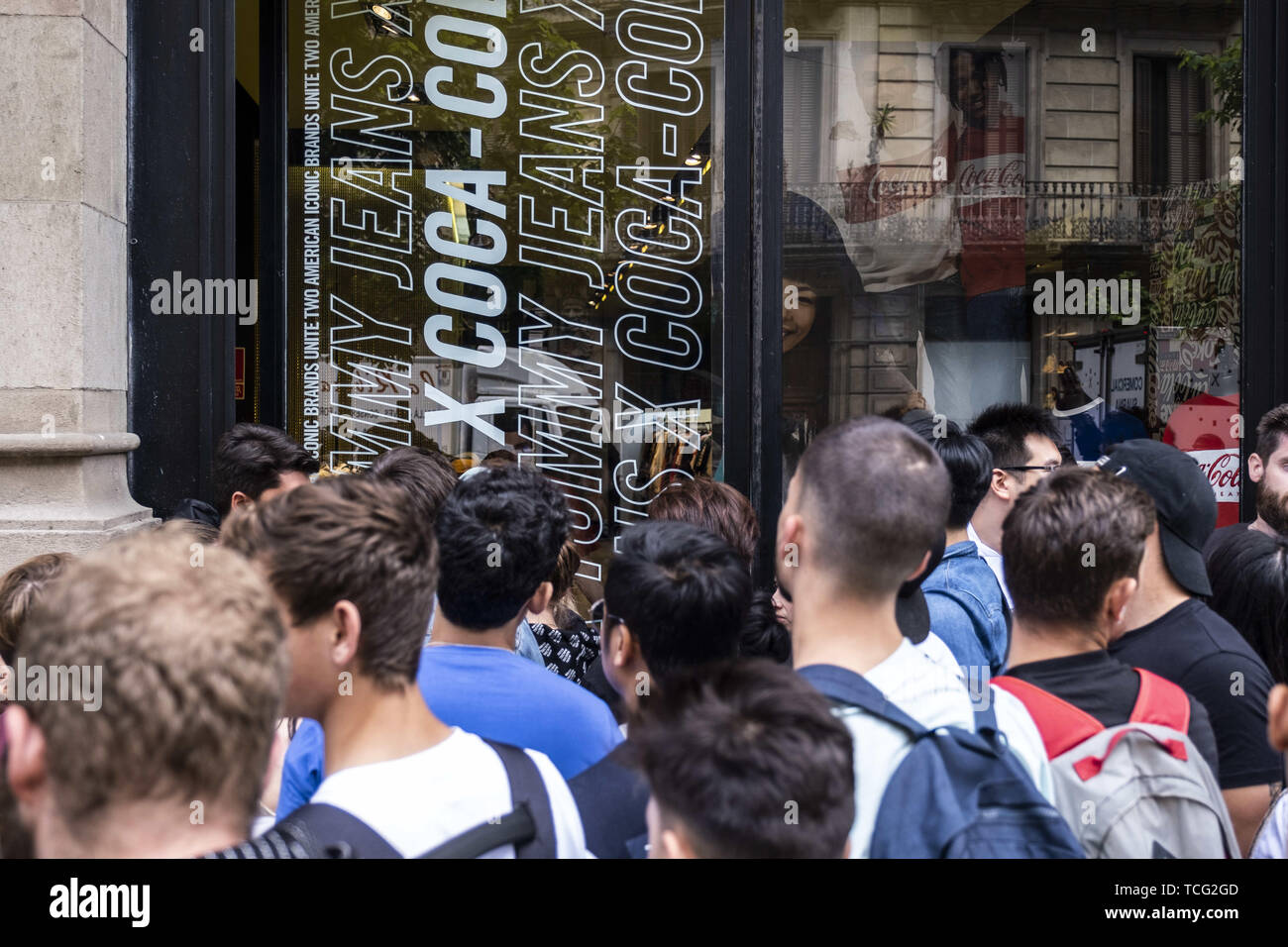 Barcelona, Catalonia, Spain. 7th June, 2019. A group of people wait infront of the shoe store for the opening hours so as to buy the new adidas shoe model.The German manufacturer of sports shoes Adidas has launched the limited edition of the Yeezy Boost 350 sports shoe model designed by rapper Kanye West. The limited production of this model has made many young people crowd in front of stores and resellers to be one of the lucky ones. Credit: Paco Freire/SOPA Images/ZUMA Wire/Alamy Live News - Stock Image