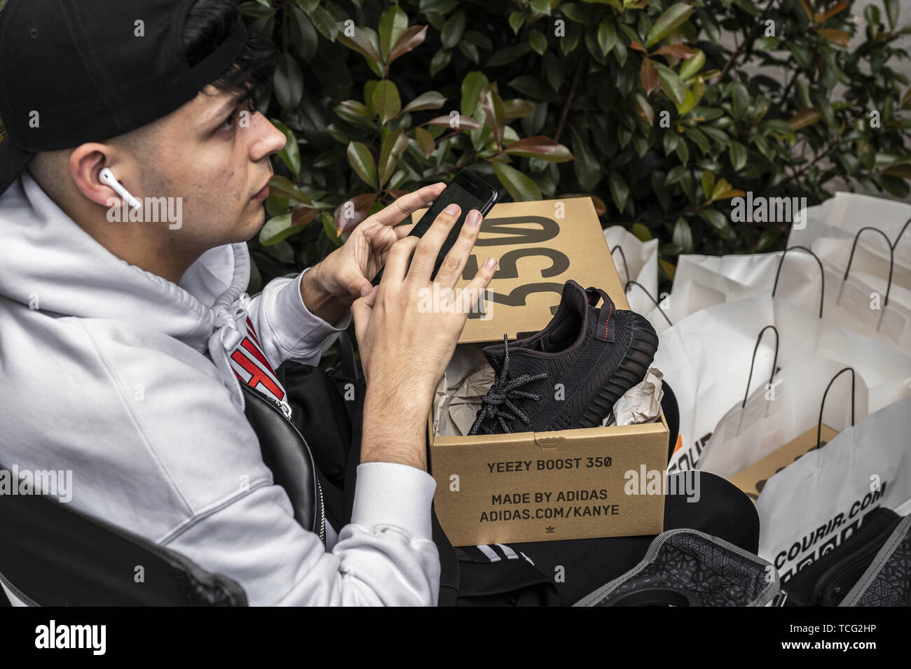 Barcelona, Catalonia, Spain. 7th June, 2019. A young man shows off his new Yeezy Boost model designed by Kanye West.The German manufacturer of sports shoes Adidas has launched the limited edition of the Yeezy Boost 350 sports shoe model designed by rapper Kanye West. The limited production of this model has made many young people crowd in front of stores and resellers to be one of the lucky ones. Credit: Paco Freire/SOPA Images/ZUMA Wire/Alamy Live News - Stock Image