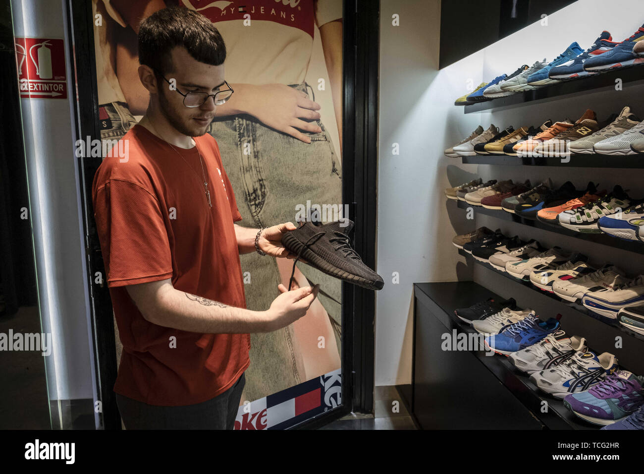 Barcelona, Catalonia, Spain. 7th June, 2019. A seller shows off the new Adidas Yeezy Boost 350 shoe model at the reseller store.The German manufacturer of sports shoes Adidas has launched the limited edition of the Yeezy Boost 350 sports shoe model designed by rapper Kanye West. The limited production of this model has made many young people crowd in front of stores and resellers to be one of the lucky ones. Credit: Paco Freire/SOPA Images/ZUMA Wire/Alamy Live News - Stock Image