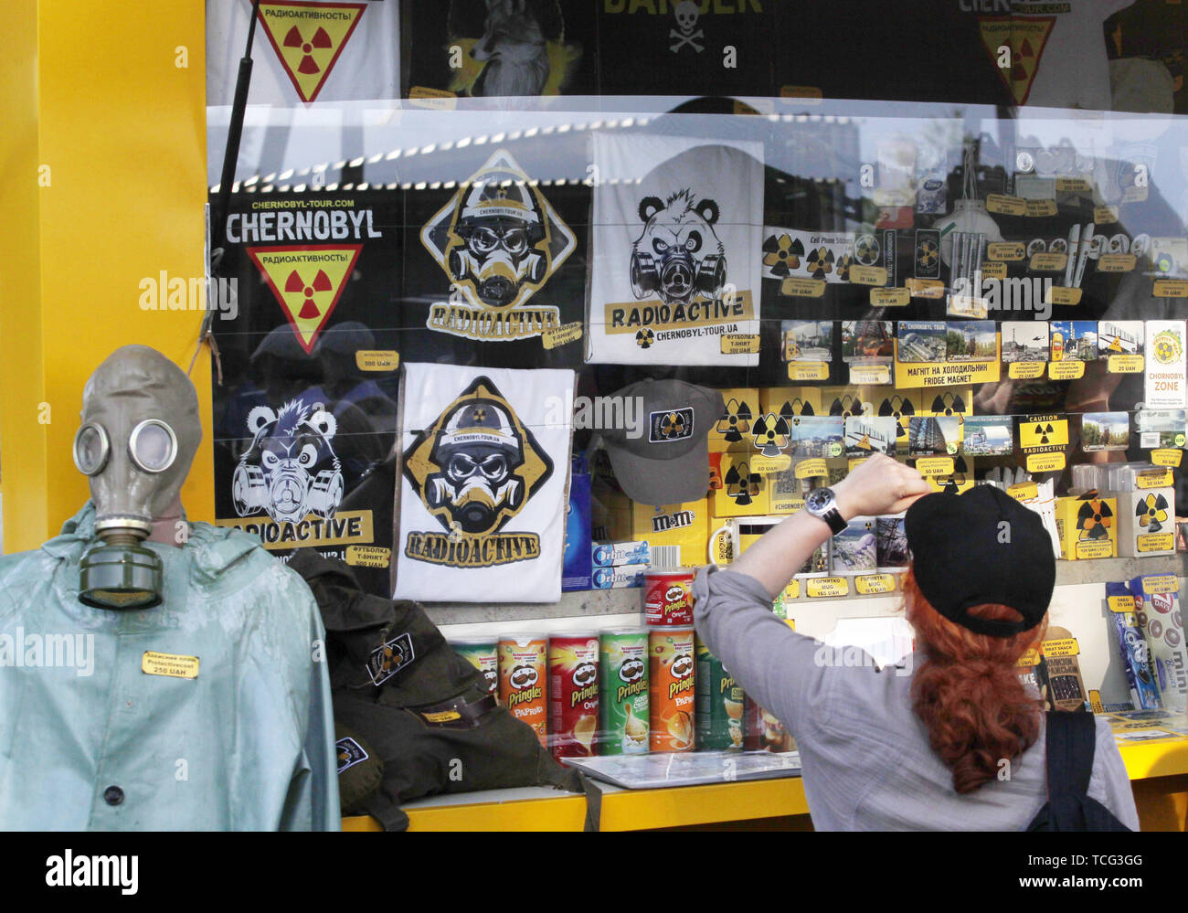 Kiev, Ukraine. 7th June, 2019. A visitor looks on a window of a Chernobyl souvenir shop at the entrance to the Chernobyl exclusion zone in Chernobyl, Ukraine, on 7 June 2019. The success of a U.S. HBO's television miniseries 'Chernobyl' has renewed interest around the world on Ukraine's 1986 nuclear disaster. Tourism to Chernobyl has spiked 40% following the debut of the HBO series in May, tour agencies reported . Last April Ukrainians marked the 33rd anniversary of the Chernobyl disaster in then-Soviet Ukraine, caused by a botched safety test in the fourth reactor of the atomic plant that - Stock Image