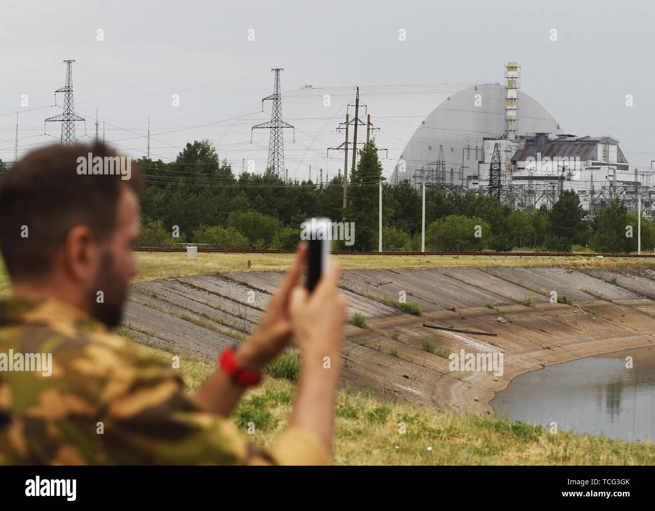 Kiev, Ukraine. 7th June, 2019. A visitor takes a photo in front the New Safe Confinement over the fourth block of the Chernobyl nuclear plant in Chernobyl, Ukraine, on 7 June 2019. The success of a U.S. HBO's television miniseries 'Chernobyl' has renewed interest around the world on Ukraine's 1986 nuclear disaster. Tourism to Chernobyl has spiked 40% following the debut of the HBO series in May, tour agencies reported . Last April Ukrainians marked the 33rd anniversary of the Chernobyl disaster in then-Soviet Ukraine, caused by a botched safety test in the fourth reactor of the atomic plant - Stock Image