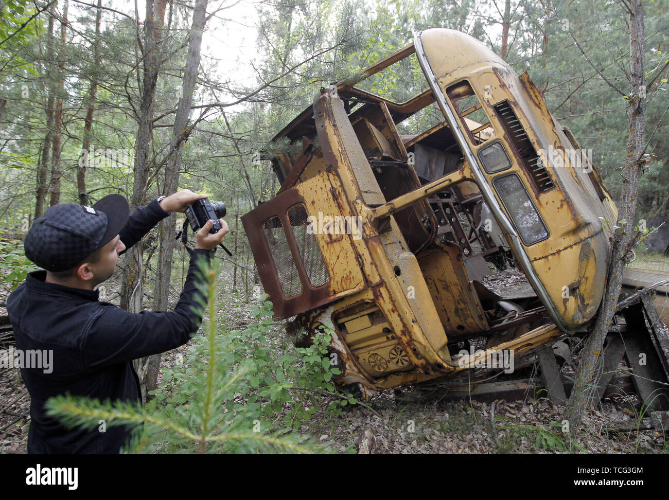 Kiev, Ukraine. 7th June, 2019. A visitor takes a photo wreckage of a bus in the abandoned city of Pripyat, near the Chernobyl nuclear power plant, Ukraine, on 7 June 2019. The success of a U.S. HBO's television miniseries 'Chernobyl' has renewed interest around the world on Ukraine's 1986 nuclear disaster. Tourism to Chernobyl has spiked 40% following the debut of the HBO series in May, tour agencies reported . Last April Ukrainians marked the 33rd anniversary of the Chernobyl disaster in then-Soviet Ukraine, caused by a botched safety test in the fourth reactor of the atomic plant that sen - Stock Image