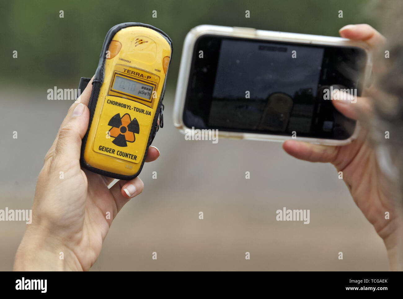 Kiev, Ukraine. 7th June, 2019. A visitor takes a photo of a geiger counter in front the New Safe Confinement over the fourth block of the Chernobyl nuclear plant in Chernobyl, Ukraine, on 7 June 2019. The success of a U.S. HBO's television miniseries 'Chernobyl' has renewed interest around the world on Ukraine's 1986 nuclear disaster. Tourism to Chernobyl has spiked 40% following the debut of the HBO series in May, tour agencies reported . Last April Ukrainians marked the 33rd anniversary of the Chernobyl disaster. Credit: ZUMA Press, Inc./Alamy Live News - Stock Image