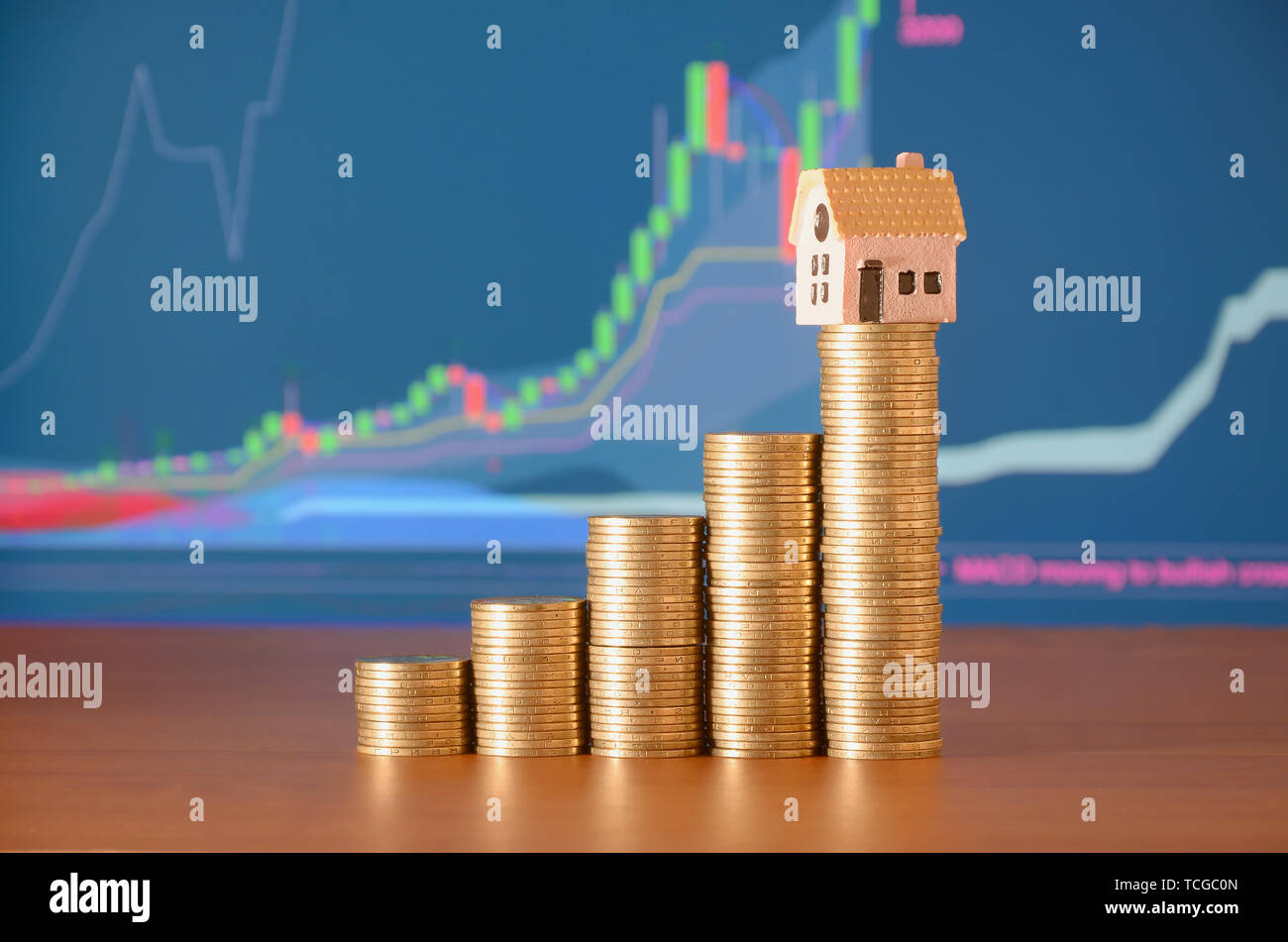 Small toy house model and coins stacks in growth graph. Planning savings money of coins to buy a home concept, mortgage and real estate investment - Stock Image