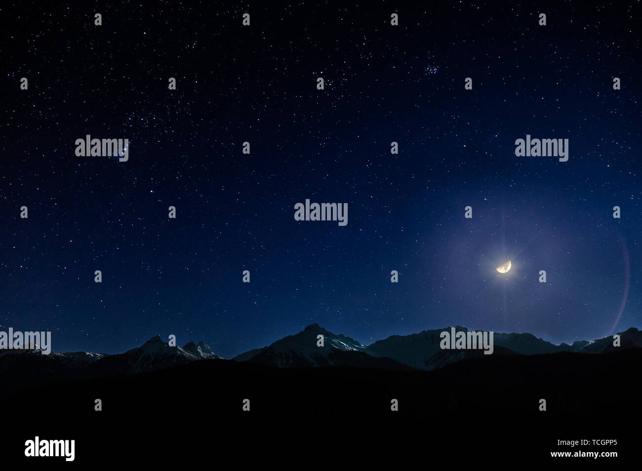 Snow covered mountain range at night under a starry sky and a bright moon. - Stock Image