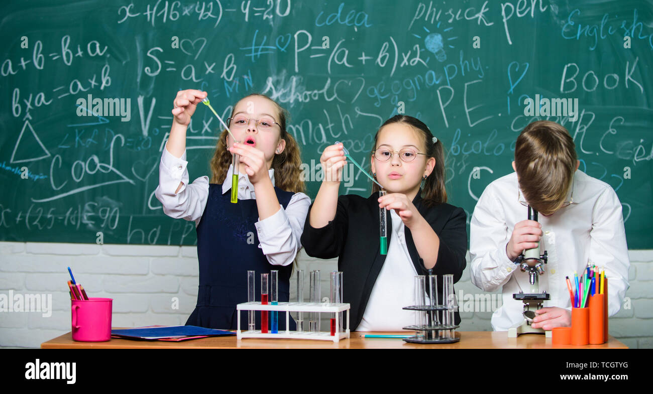 Little children at school lesson. students doing experiments with microscope. happy childrens day. Chemistry. Back to school. Little kids learning chemistry in school lab.What seems to be a problem - Stock Image