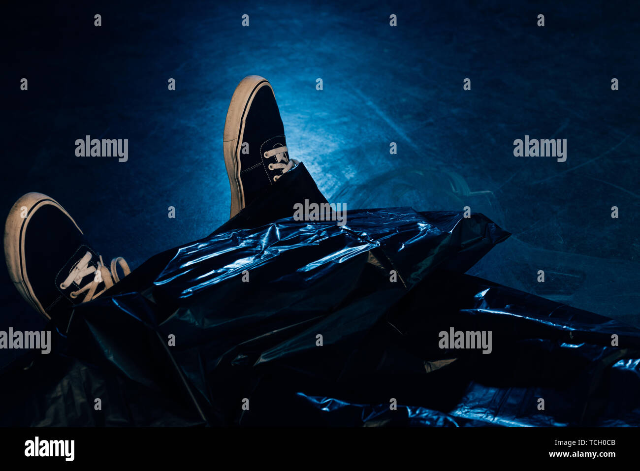 partial view of covered dead body at crime scene Stock Photo