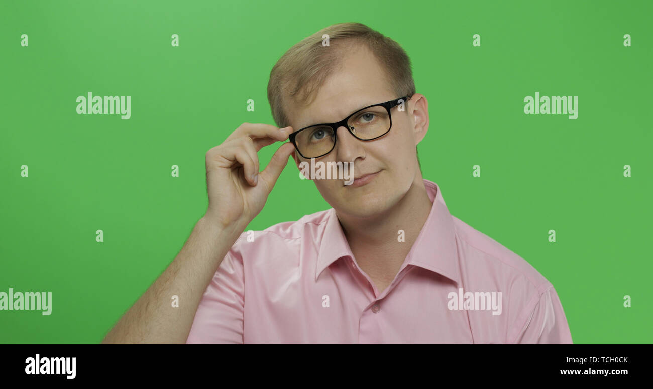 Handsome young man in the pink shirt and glasses looking in the camera on the chroma key background. Green screen. - Stock Image