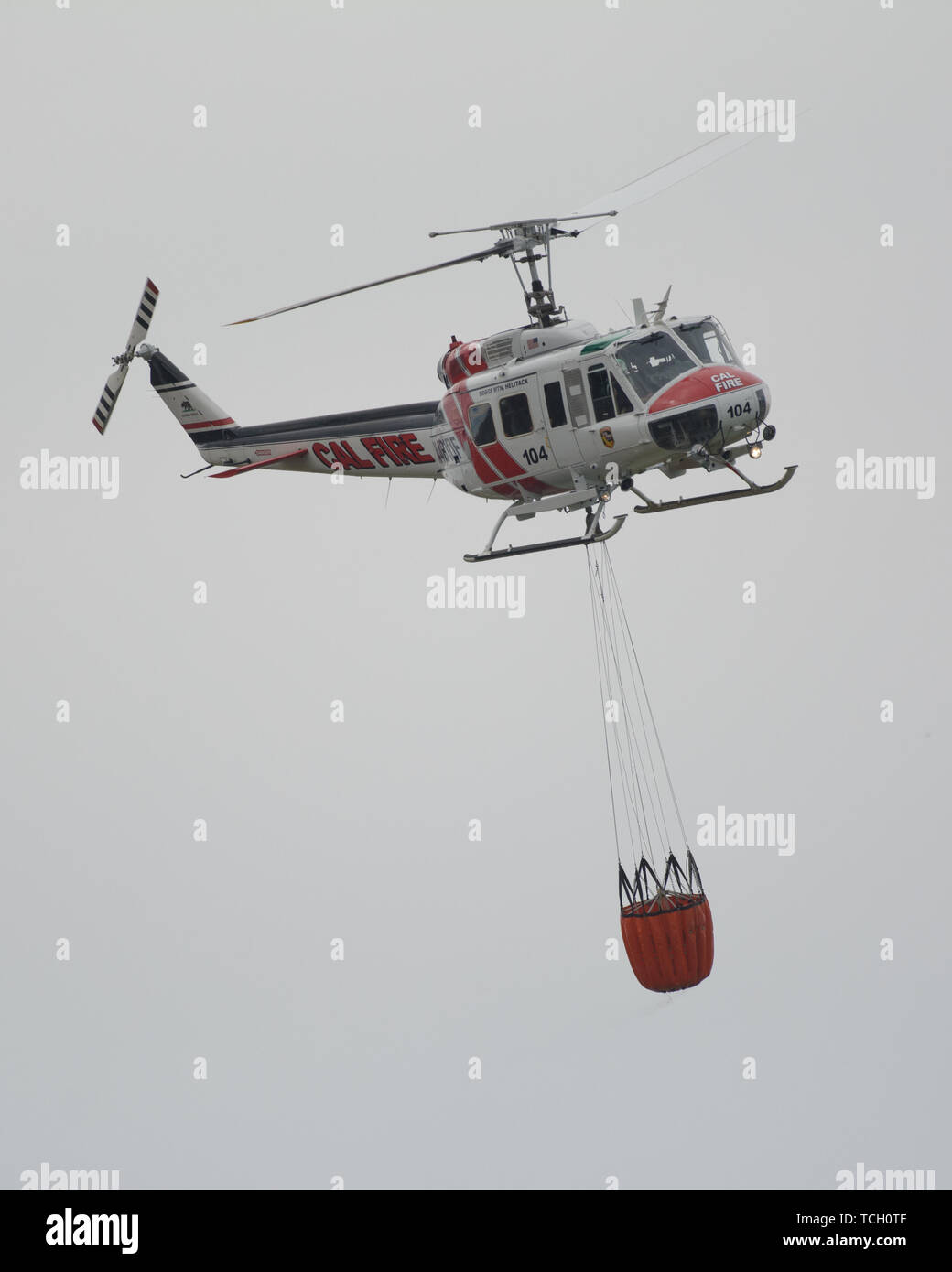 A Cal Fire helicopter flying around with water bucket in lake berryessa, california, usa - Stock Image