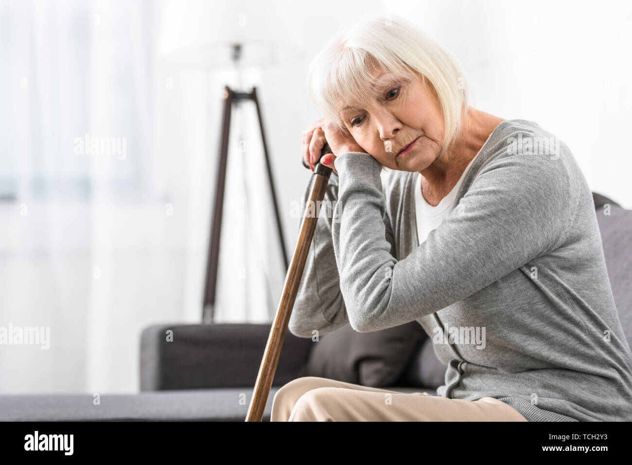 pensive senior woman with wooden cane sitting on sofa in living room Stock Photo