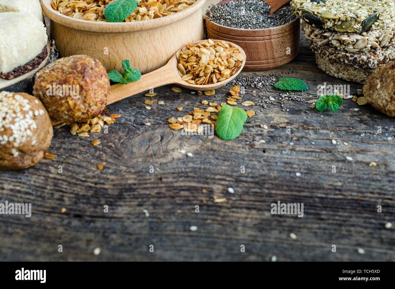 Healthy snacks. Fitness dietary food. Sesame halva. Flakes, chia seeds in two bowls and spoons. Kozinaki with sesame, peanuts, sunflower, pumpkin seed - Stock Image