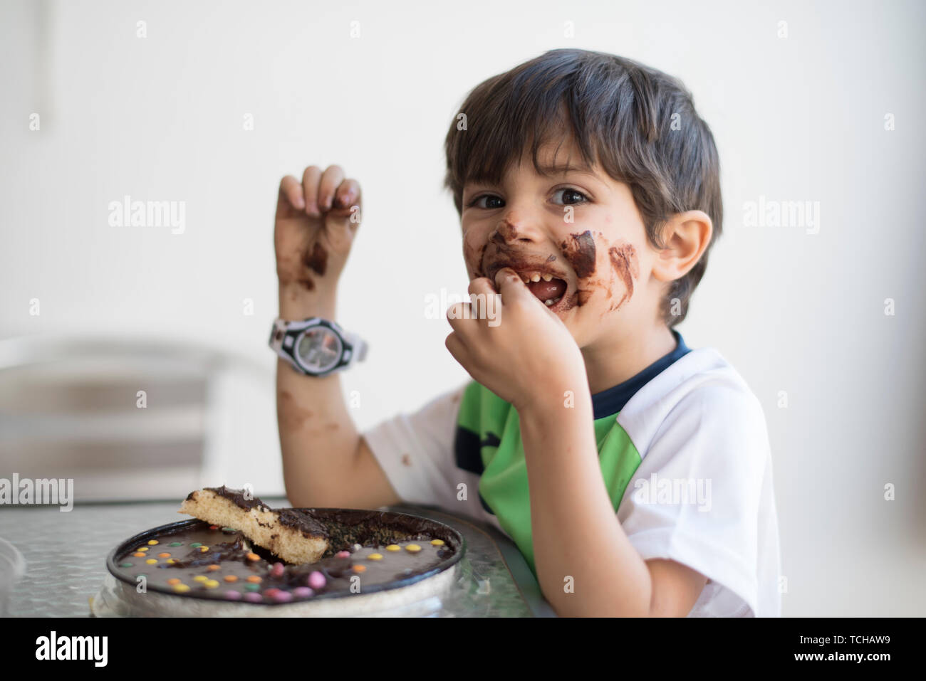 Dirty kid eating chocolate pie - Stock Image