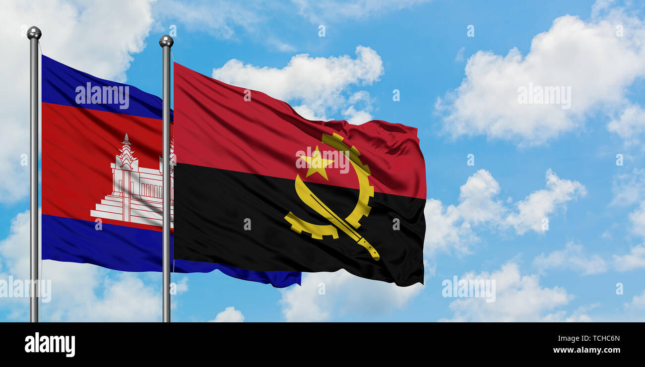 Cambodia and Angola flag waving in the wind against white cloudy blue sky together. Diplomacy concept, international relations. - Stock Image